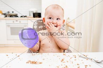 Little baby eating at kitchen. Happy messy eater