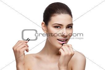 Beautiful girl applying pink lipstick