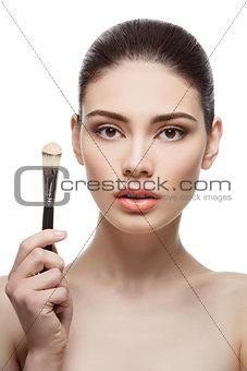 Beautiful girl holding foundation brush