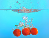 red tomatoes dropped into water