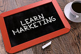 Learn Marketing Handwritten by white Chalk on a Blackboard.