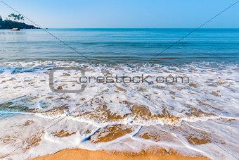 wave with sea foam on a sandy beach