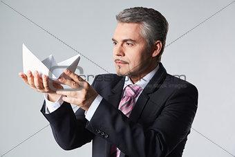 Portrait of businessman holding paper boat
