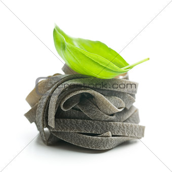 black tagliatelle pasta and basil leaf