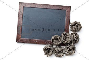 black tagliatelle pasta and chalkboard