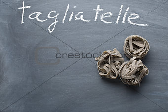 black tagliatelle pasta on chalkboard