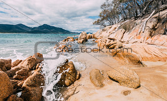 A wave crashing on rocks in a national park in Tasmania, with mountains in the background
