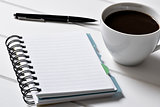 blank notebook, pen and cup of coffee