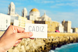 man shows a signboard with the word Cadiz, in Cadiz, Spain