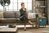 Elegant brunet business woman is sitting on couch in loft