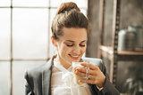 Smiling businesswoman enjoying cup of coffee latte macchiato