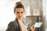 Portrait of business woman holding tablet in loft apartment