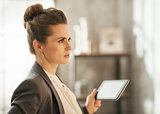Concentrated businesswoman holding tablet in loft apartment