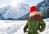 Child in green coat standing in the front of snowy mountains