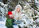 Happy mother and child outdoors among snowy spruces