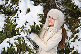 Happy young woman standing outdoors near snowy spruce branch