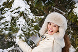Smiling woman standing outdoors and shaking snowy spruce branch