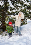 Mother shaking snow off branch on child while standing outdoors