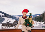 Happy woman with Christmas tree on balcony overlooking mountains