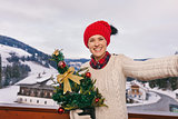 Happy young woman with Christmas tree taking selfie on balcony
