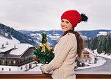 Happy woman with Christmas tree on balcony overlooking mountains