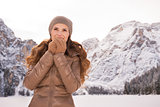 Woman warming hands outdoors among snow-capped mountains