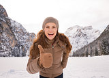 Woman showing thumbs up outdoors among snow-capped mountains