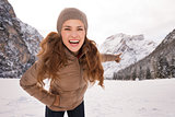 Happy young woman outdoors pointing on snow-capped mountains