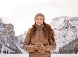 Woman with snowball outdoors among snow-capped mountains