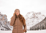 Woman talking mobile phone outdoors among snow-capped mountains