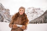 Woman outdoors among snow-capped mountains writing sms
