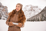 Young woman with cell phone outdoors among snow-capped mountains
