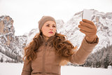 Woman taking photo outdoors among snow-capped mountains