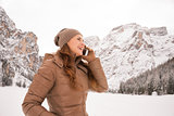 Woman talking cell phone outdoors among snow-capped mountains