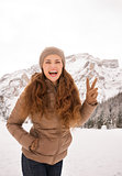 Woman showing victory outdoors among snow-capped mountains