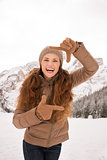 Woman framing with hands outdoors among snow-capped mountains