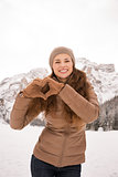 Woman showing heart shaped hands among snow-capped mountains