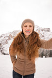 Woman taking selfie outdoors among snow-capped mountains