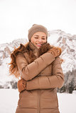 Happy young woman outdoors among snow-capped mountains