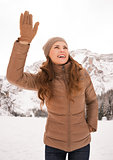 Happy woman outdoors among snow-capped mountains calling someone