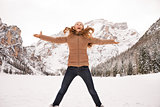 Happy young woman jumping outdoors among snow-capped mountains