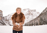 Smiling woman with snowball outdoors among snow-capped mountains
