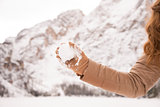 Closeup on throwing snowball woman among snow-capped mountains