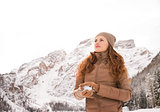 Young woman making snowball outdoors among snow-capped mountains