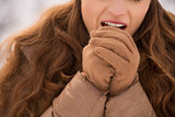 Closeup on woman warming hands with breathe in winter outdoors