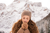 Woman warming hands with breathe among snow-capped mountains