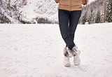 Closeup on legs of woman outdoors among snow-capped mountains