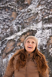 Smiling woman outdoors among snow-capped mountains looking up