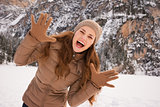 Portrait of cheerful woman outdoors among snow-capped mountains