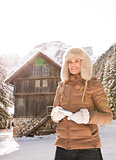Woman with smartphone standing near cosy mountain house